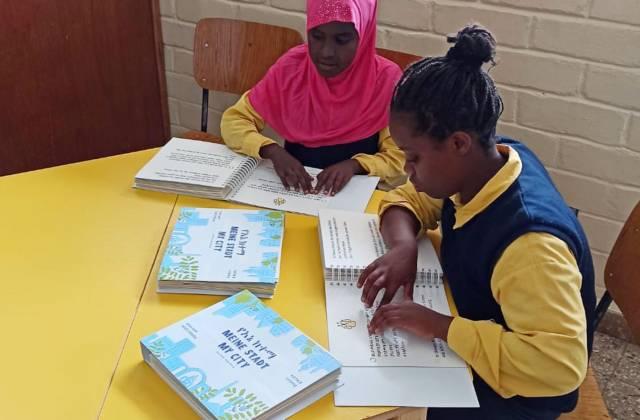zwei Mädchen lesen Brailleschrift