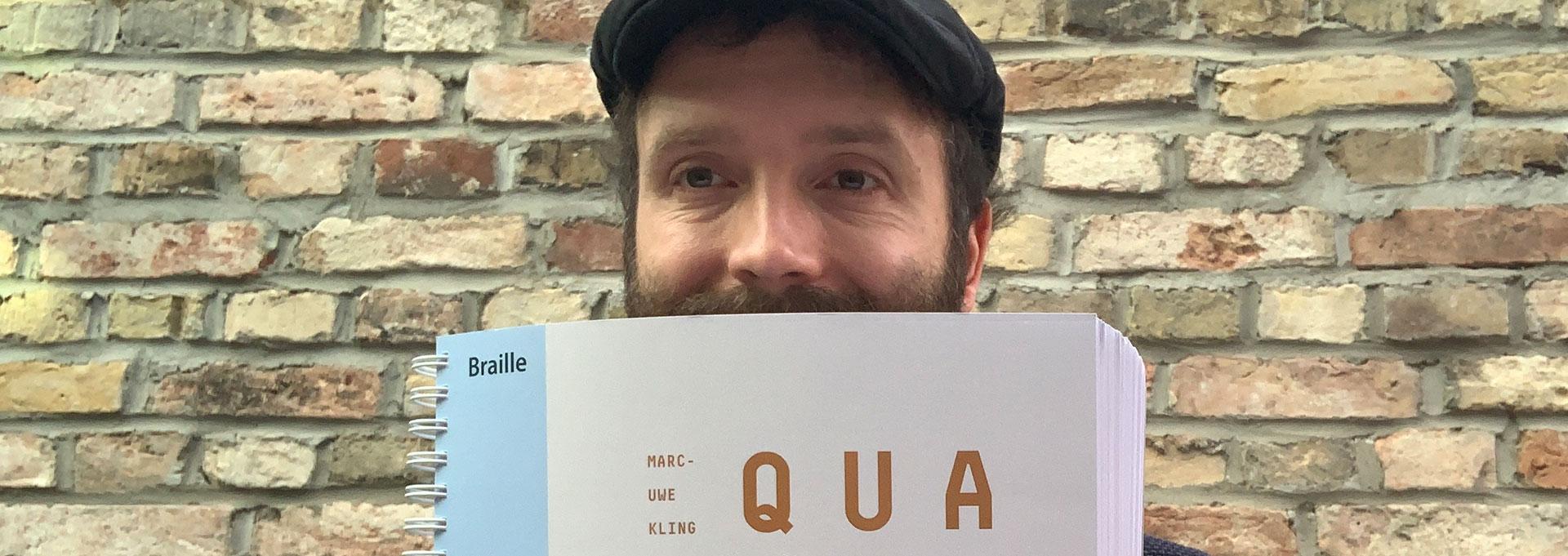 """Marc-Uwe-Kling mit dem übertragenen Braille-Buch """"Qualityland"""""""